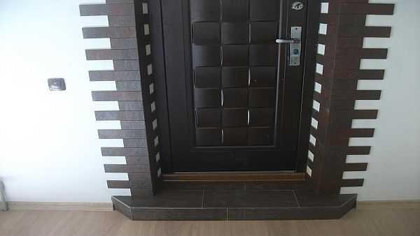 Наружный откос входной двери можно отделать камнем или плиткой