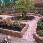 Керамический кирпич разного цвета и дорожки посыпанные подкрашенным гравием и двор с клумбой смотрится замечательно