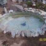Следующий этап изготовления мини-пруда для дачи - декорирование краев камнями