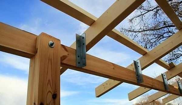 Один из способов крепления стропильных ног веранды к верхней обвязке: на металлические уголки