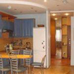 Плитка на полу имеет разные цвета,, также разделение гостиной и кухни поддерживается разноуровневым потолком