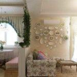 Оригинальная идея зонирования совмещенной кухни и столовой - часть стены и вьющиеся растения