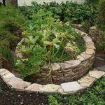 Ограда для грядок сложена из плитняка - пиленного природного камня