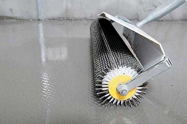 Валик для раскатки жидких полов сделан из пластика, на концах его иголки