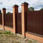Этот забор сделан из кирпича (цоколь и столбы) и профнастила.