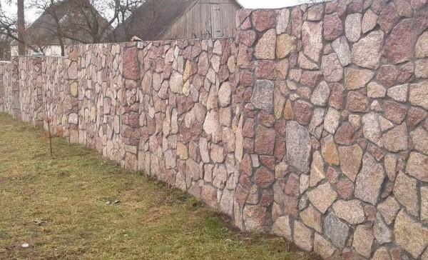 Каменный забор. Этот точно сложен из камня и правильно забутован: между камнями немного раствора, а это говорит о хорошем качестве работы