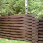 Дощатый забор: доски изогнуты между столбами - красиво и недежно