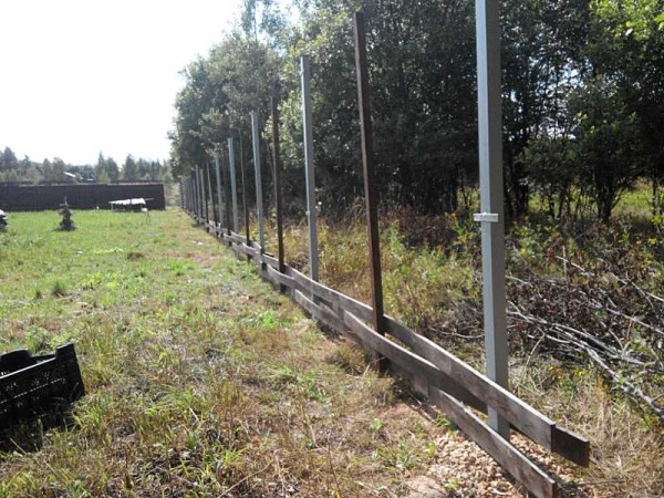 Ограду-плетенку из досок удобнее собирать не прогонами, а горизонтально - по несколько досок вплетая по всей длине