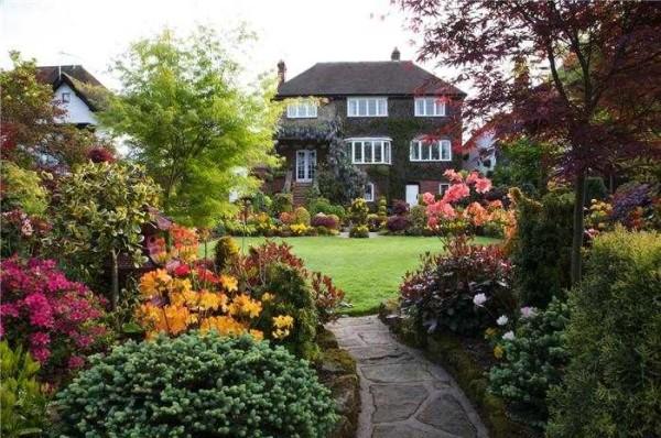 Пышная растительность перемежается ухоженными газонами - признаки английского сада