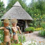 Беседка, крытая камышом и скульптуры из керамических горшков  - интересные дизайнерские находки в оформлении сада