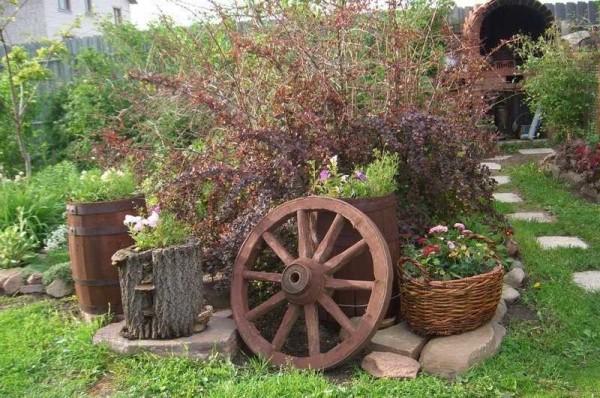 Оформление сада в деревенском стиле легко узнать по наличию колес от телег, корзин, керамической посуды, Которая используется в самых неожиданных ипостасях