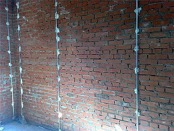 Установленные маяки под штукатурку на кирпичной стене