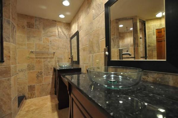 На стенах - натуральный камень, необычная мебель и стеклянная раковина - стильный интерьер