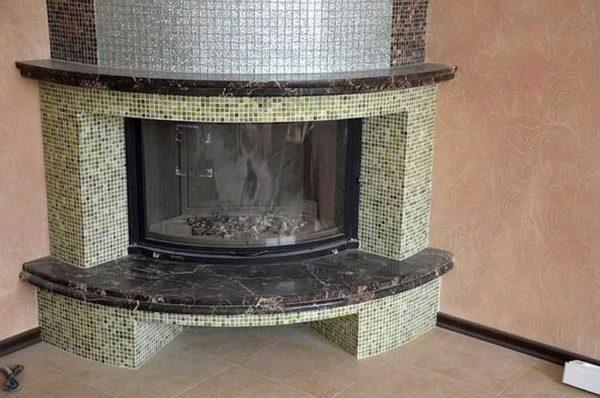 Отделка камина мозаикой особенно хороша на округлых формах, где другие материалы применять очень проблематично