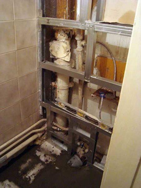 Если трубы находятся на задней стенке, а туалет узкий и длинный, имеет смысл зашить заднюю стенку полностью