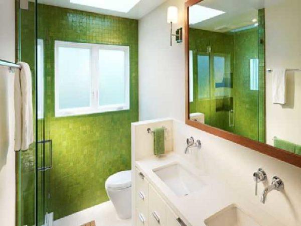 Зеленая стенка из мозаики в маленькой ванной комнате освежает интерьер