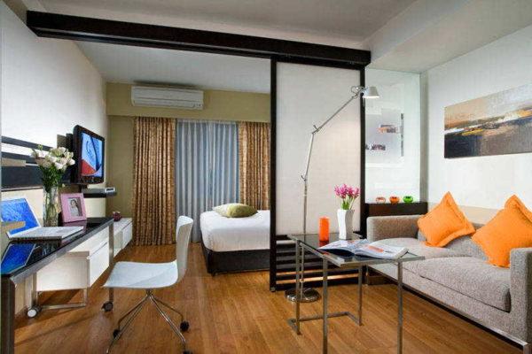 Кровать в гостиной с выделенной спальней размещают как правило, подальше от входа
