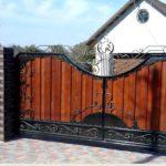 Представитель второго типа — кованные ворота и забор зашиты досками