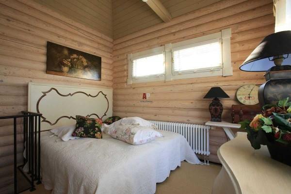 Оформление спальни в домах из бревна ничем не отличается: светлые, спокойные тона и несколько цветовых акцентов