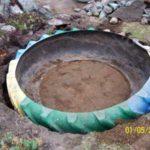 Обрезанную покрышку устанавливают в выкопанную яму, засыпают внутрь немного земли, выравнивая дно