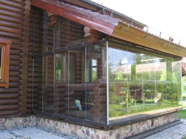 Безрамное остекление веранды в сочетании с бревенчатым домом - не самое лучшее решение