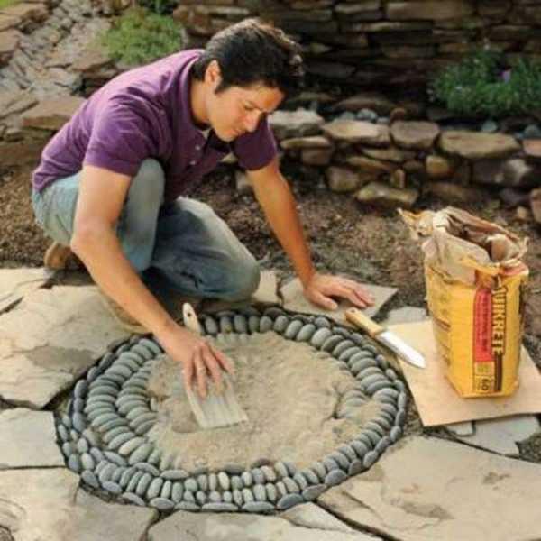 Засыпают готовый узор смесью песка и цемента