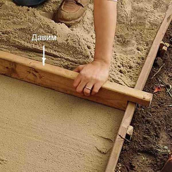 Один из способов выровнять песок под дорожку. Но необходимо вкопать предварительно доски и выставить их по уровню. Потом делают такую заготовку и песок выравнивают, протягивая ее по направляющим