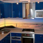 Синяя кухня органично дополняется пластиковым фартуком, на котором запечатлен рассвет