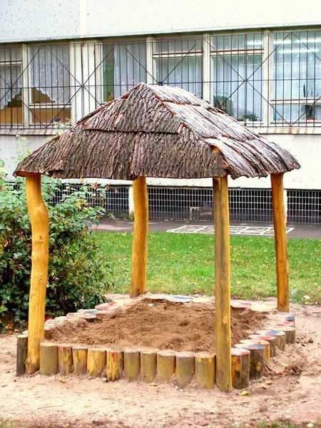 Песочница из пеньков под крышей