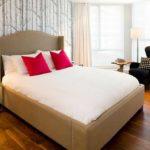 Едва заметный рисунок на стене, но яркие подушки на кровати