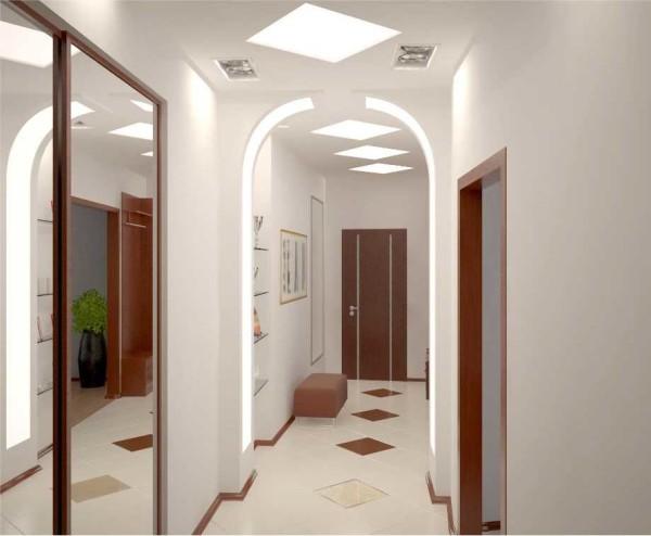 Длинный коридор разбивают на зоны освещением и арками из гипсокартона - так он выглядит не таким унылым и однообразным