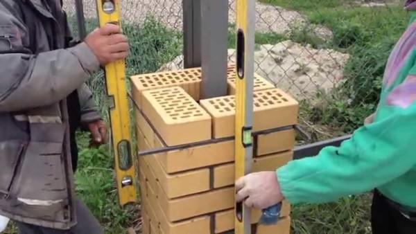 Кладка столбов для забора ведется вокруг металлической армирующей трубы