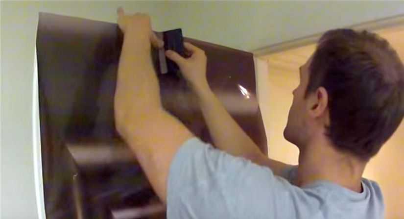 Прикладываем пленку к верхней кромке дверного полотна и разглаживаем, удаляя воздух