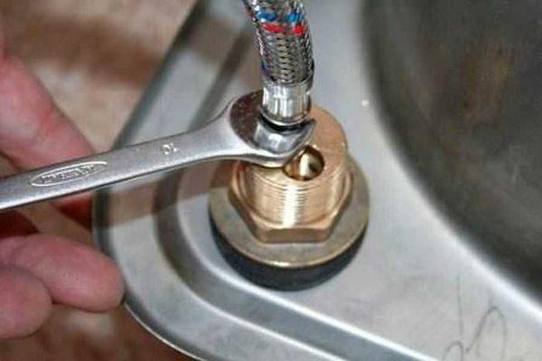 Вкручиваем гибкую подводку в отверстия на корпусе смесителя, затягиваем слегка ключом