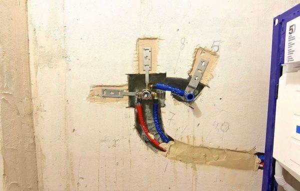 В стене прокладывают подводящие трубы, устанавливают закладной элемент, к которому затем крепиться наружная часть смесителя