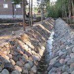 Чтобы стенки открытых дренажных канав не осыпались, на склонах высаживают почвопокровные растения или выкладывают их булыжниками