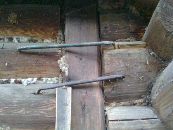 Такие скобы надо установить внизу, скрепив несколько нижних венцов, или в месте крепления пристроек, если они поднимаются вместе с домом