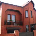 Фасад двухэтажного дома из красного кирпича с характерными чертами современного стиля, но явным индивидуальным характером