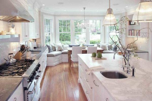 Дизайн кухни с эркером большой площади: островная кухня и диван