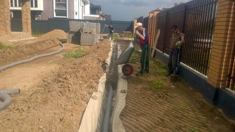 Забор с фундаментом на участке с уклоном требует устройство отведения воды
